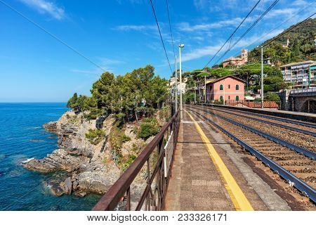 Platform on small local station and railroad tracks along beautiful  Mediterranean coastline in Liguria, Italy.