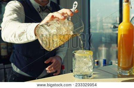 Mixologist is making cocktail on rocks, straining from mixing glass, toned image