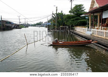 Wooden Long Boat Floating On The River Of Countryside In Thailand