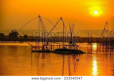 Fisherman Working On Bamboo Scaffolding With Traditional Bamboo Fishing Tools In Swamp In Evening Ti
