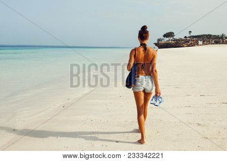View From Back Young Tanned Woman With A Backpack Walking Along Ocean Shoreline Morning At Dawn
