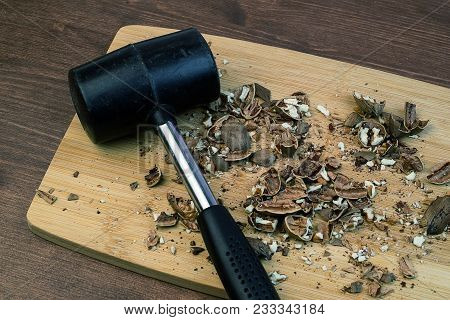 Among The Crumbled Pecan Nuts Is A Hammer On A Cutting Board, Inaccurately Shredded Nuts
