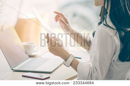 Cropped Image Of Businesswoman Holding Document Paper While Working At Office