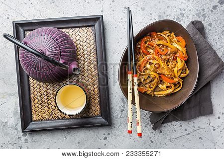 Asian Food, Stir Fry Udon Noodles With Meat And Vegetables In A Bowl On Gray Stone Background, Top V