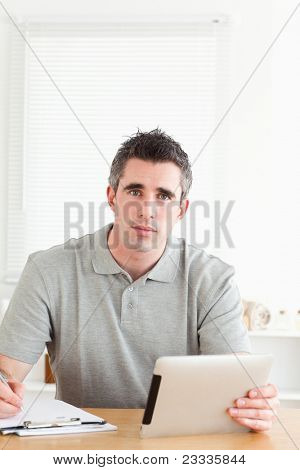 Doctor sitting working with a tablet and a chart in a room