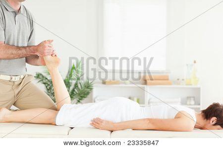 A masseur massages a female customer's leg