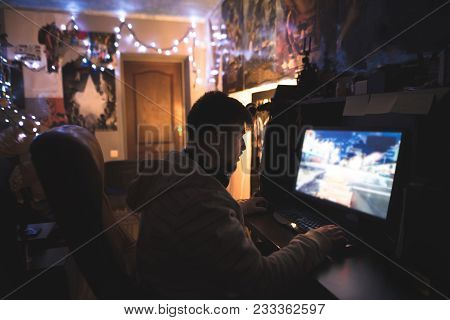 Gamer With Beard Plays Games On A Home Computer. A Young Man Sits At Home In His Room And Plays Game