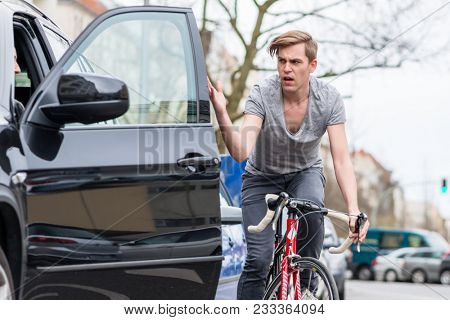 Angry young bicyclist shouting while swerving for avoiding dangerous collision with the open door of a 4x4 car on a busy street in the city poster