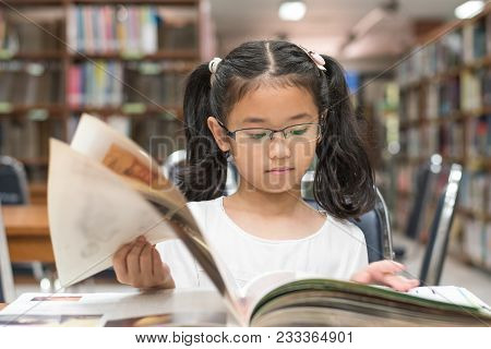 School Education And Literacy Concept With Asian Girl Kid Student Learning And Reading Book In Libra