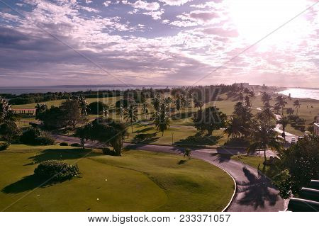 Golf Course At Sunset. The Green Golf Course Is Seated With Palm Trees Against The Backdrop Of An In