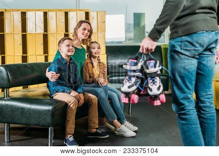 Selective Focus Of Family Looking At Man With Roller Skates For Skating In Skate Park