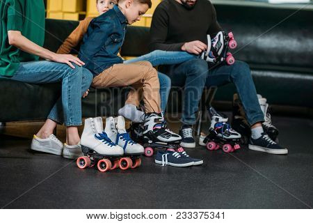 Partial View Of Family Wearing Roller Skates Before Skating In Skate Park