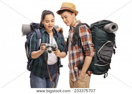 Female teenage tourist showing pictures on a camera to a male tourist isolated on white background