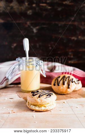 Home Baked Sweet Buns Called Scones With Lemon Vanilla Custard And Chocolate On A Wooden Table, Sele