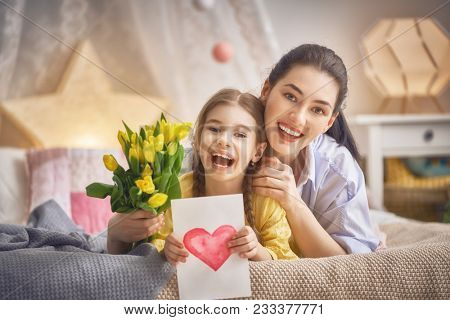 Happy women's day! Child daughter is congratulating mom and giving her flowers tulips. Mum and girl smiling and hugging. Family holiday and togetherness.
