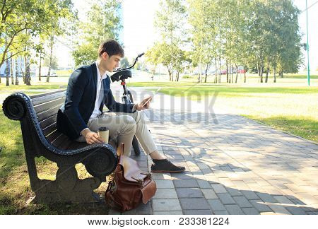 Businessman On A Coffee Break. He Is Sitting On A Bench And Working At Touchpad, Next To Bike