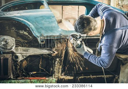 Young Man Mechanical Worker Repairing Old Vintage Car Body With Electric Grider In Messy Garage - Wo