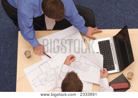 Male Architects Going Over The Details Of Blueprint