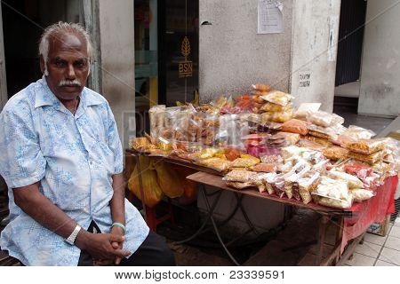 KUALA LUMPUR - MAY 22: An Indian trader sells snack food on May 22, 2011 in Kuala Lumpur, Malaysia. The snack food includes roasted peanuts, beans and a deep fried spiced flour strips known as muruku.