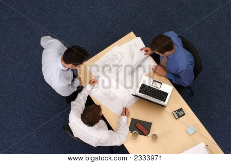 Three Working Business People Over Plans