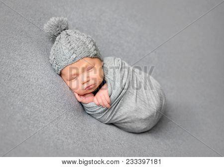 Newborn baby sleeping curled up in grey blanket