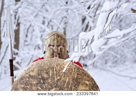 Spartan Warrior Wearing Red Cape Is Looking In Camera Standing In White Dense Winter Forest. He Has