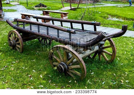 Gypsy cart. Old cart on green grass in the back of the house on summer day.