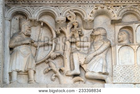 MODENA, ITALY - JUNE 04: Plate with stories from Genesis: Blind Lamech kills Cain with an arrow in his throat, bass relief by Wiligelmo, Modena Cathedral, Italy on June 04, 2017.