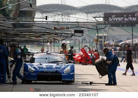 SEPANG - JUNE 19: Pit crew works on Team Impul's Nissan GT-R R35 car during the practice round of the Japan SUPER GT Round 3 race on June 19, 2011 in Sepang international Circuit, Malaysia.