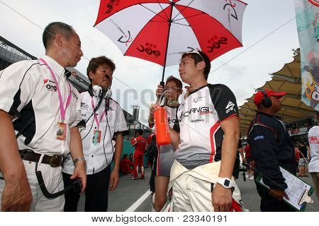 SEPANG, MALAYSIA - JUNE 19: Team SG Changi mechanics discuss team tactics before the start of the Japan SUPER GT Round 3 race on June 19, 2011 in Sepang international Circuit, Sepang, Malaysia.