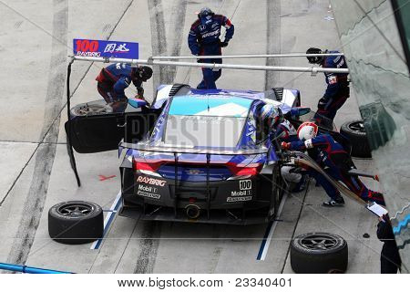 SEPANG, MALAYSIA - JUNE 19: Team Kunimitsu's pit-crew works on the car during pit-stop at the Sepang International Circuit before the Japan SUPER GT Round 3 race on June 19, 2011 in Sepang, Malaysia.
