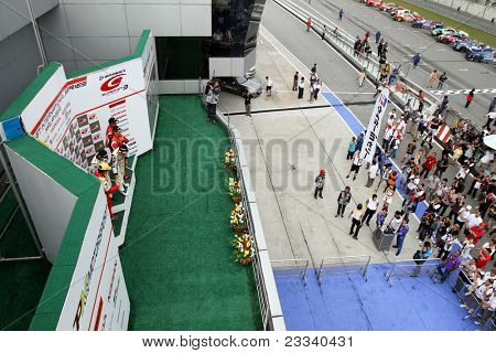 SEPANG, MALAYSIA - JUNE 19: Winners of the GT300 SUPER GT race pose on the podium and celebrate with team and fans at the Sepang International Circuit on June 19, 2011 in Sepang, Malaysia.
