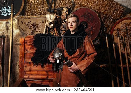 Serious militant Viking sits on the throne with a weapon in his hands. Portrait of a warrior in ancient clothes with a gun against the backdrop of skins and flags of the Vikings. poster