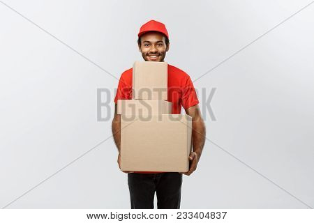 Delivery Concept - Portrait Of Happy African American Delivery Man In Red Cloth Holding A Box Packag