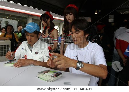 SEPANG - JUNE 19: Atsushi Yogo and Manabu Orido (cap) of JLOC sign autographs for fans at the Sepang International Circuit during the Japan SUPER GT Round 3 event on June 19, 2011 in Sepang, Malaysia.