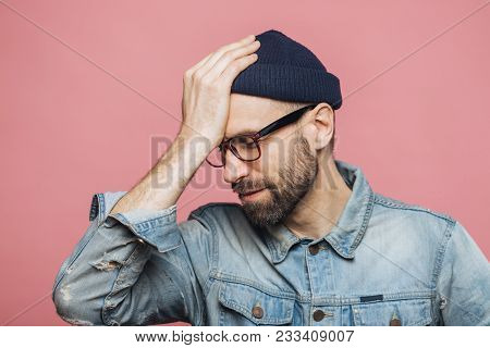 Horizontal Portrait Of Stressful Stylish Unshaven Male Regrets Something, Keeps Hand On Head, Looks