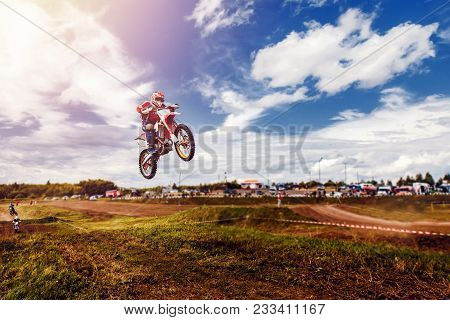 Racer On Dirtbike Motorcycle Jumps And Takes Off Over The Track, In Background Opponent Is Catching