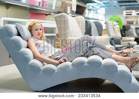 Caucasian Woman Shopping For Sofa Chair And Home Decor In Furniture Store. Lady Lying On Sofa, Relax