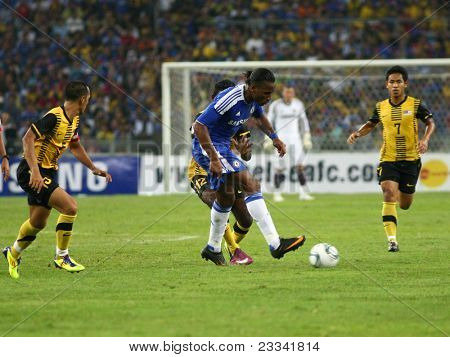 BUKIT JALIL, MALAYSIA - JULY 21: Chelsea's Didier Drogba (blue) passes the ball as Malaysian players surround him at the National Stadium on July 21, 2011 in Bukit Jalil, Malaysia. Chelsea won 1-0.
