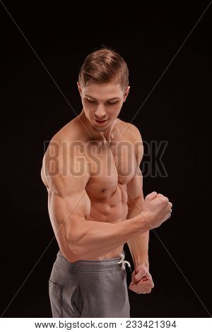 An Athlete With Perfect Muscles And Posture. A Bodybuilder Showing Off Biceps And Triceps On A Black