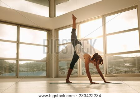 Fit Woman Practicing Downward Facing Dog Pose With One Leg Stretching Upward In Fitness Studio. Fitn