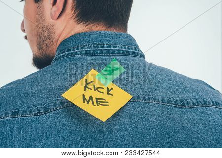 Back View Of Man With Note On Sticky Tape With Kick Me Lettering On Back, April Fools Day Holiday Co