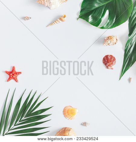 Summer Tropical Composition. Frame Made Of Green Tropical Leaves And Sea Shells On Gray Background.