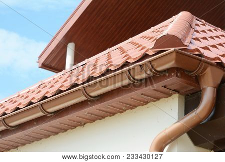 Close up on roof gutter holder and guttering downspout pipe with clay tiles roof. Installing rain gutter. poster
