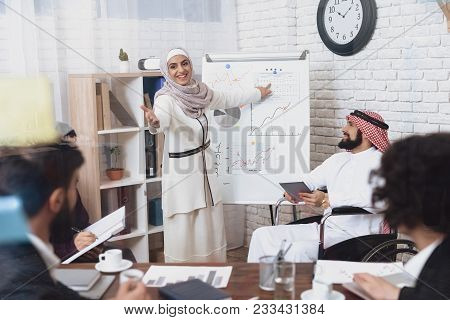 Disabled Arab Man In Thawb In Wheelchair Working In Office. Man And Female Coworker Are Showing Char