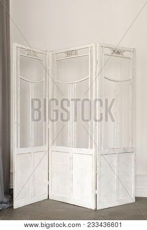 White Delicate Decorative Wood Panel On White Plaster Wall. Boudoir Wedding Room. Retro Folding Scre