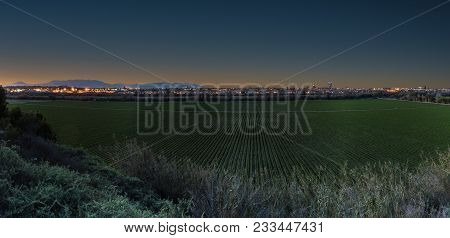Panoramic View At Dawn As Gradient Orange Color Rises In Horizon Behind City Lights With Agriculture