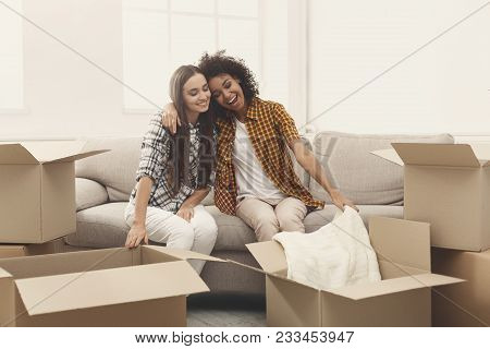 Two Happy Young Women Unpacking Moving Boxes In New Apartment, Viewing Online Order, Copy Space
