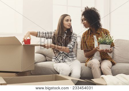 Two Young Women Unpacking Moving Boxes In New Apartment, Viewing Online Order, Holding Green Plant A
