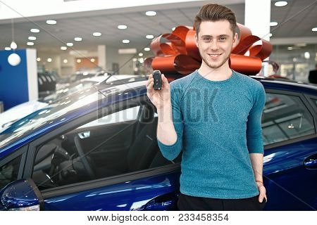 Young Man Is Showing A Key, Looking At Camera And Smiling While Standing Near The Car In Car Dealers